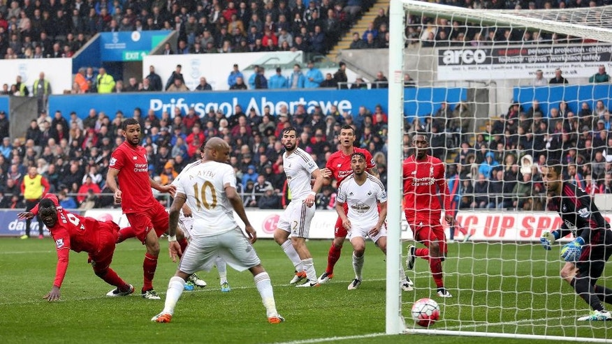Liverpool's Christian Benteke, left, scores his side's first goal of the game  during the English Premier League soccer match between Swansea City and Liverpool,  at the Liberty Stadium, in Swansea, Wales,  Sunday May 1, 2016. (David Davies/PA via AP) UNITED KINGDOM OUT