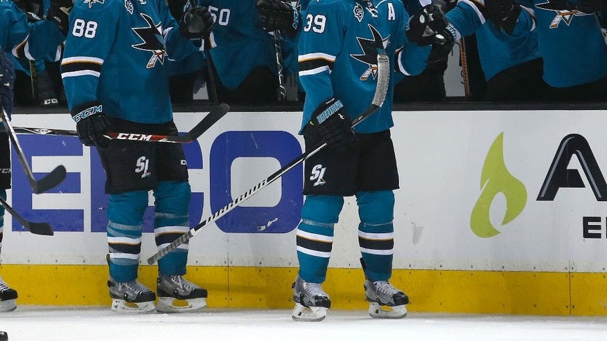 San Jose Sharks' Logan Couture, right, and Brent Burns (88)) are congratulated after Couture goal against the Nashville Predators during the second period of Game 2 in an NHL hockey Western Conference semifinal series Sunday, May 1, 2016, in San Jose, Calif. (AP Photo/Tony Avelar)