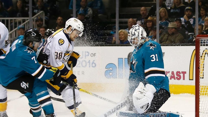 San Jose Sharks goalie Martin Jones (31) stops a shot by Nashville Predators right wing Viktor Arvidsson (38) as San Jose Sharks defenseman Paul Martin (7) defends during the second period of Game 2 in an NHL hockey Western Conference semifinal series Sunday, May 1, 2016, in San Jose, Calif. (AP Photo/Tony Avelar)