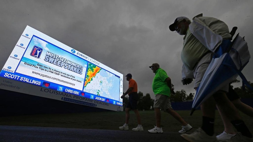 Spectators walk past a sign showing a looming storm front approaching, after the third round of the PGA Zurich Classic golf tournament was postponed due to the weather at TPC Louisiana in Avondale, La., Sunday, May 1, 2016. (AP Photo/Gerald Herbert)