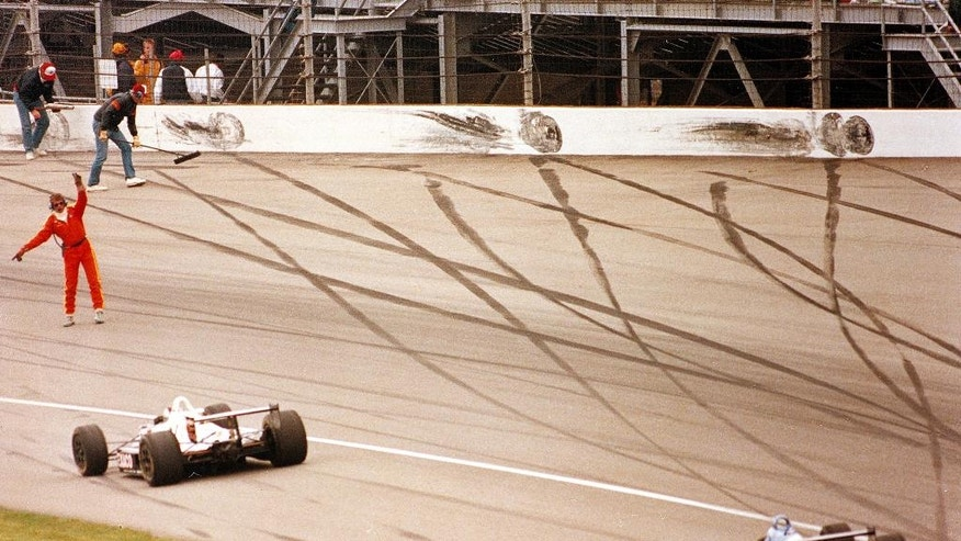 FILE - In this May 24, 1992 file photo, track workers clean up debris after a series of crashes in Turn 2 at the Indianapolis Motor Speedway during the 76th running of the Indianapolis 500 auto race at Indianapolis Motor Speedway in Indianapolis, Ind. (AP Photo/Amy Sancetta, File)