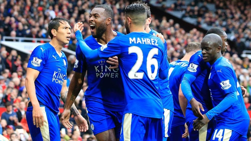 Leicester's Wes Morgan, second left, celebrates with teammates after scoring during the English Premier League soccer match between Manchester United and Leicester at Old Trafford Stadium, Manchester, England, Sunday, May 1, 2016. (AP Photo/Jon Super)