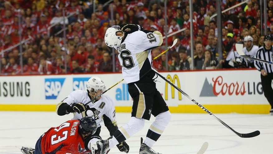 Pittsburgh Penguins right wing Eric Fehr (16) is hit by  teammate Evgeni Malkin's (71) stick after colliding with Washington Capitals right wing Tom Wilson (43) and losing the puck during the first period of Game 2 in an NHL hockey Stanley Cup Eastern Conference semifinals Saturday, April 30, 2016 in Washington. (AP Photo/Pablo Martinez Monsivais)