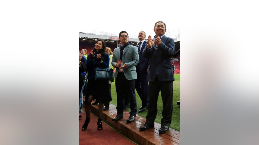 Leicester's Thai owner Vichai Srivaddhanaprabha, right, and his son Aiyawatt, centre, applaud the crowd after their team's 1-1 draw at Manchester United during the English Premier League soccer match between Manchester United and Leicester at Old Trafford Stadium, Manchester, England, Sunday, May 1, 2016. (AP Photo/Jon Super)