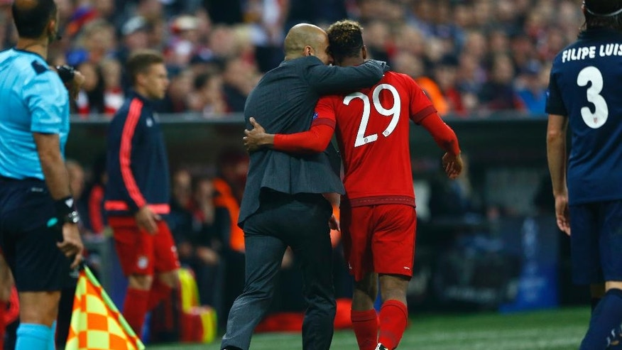 Bayern's head coach Pep Guardiola speaks with Bayern's Kingsley Coman during the Champions League second leg semifinal soccer match between Bayern Munich and Atletico de Madrid in Munich, Germany, Tuesday, May 3, 2016. (AP Photo/Matthias Schrader)