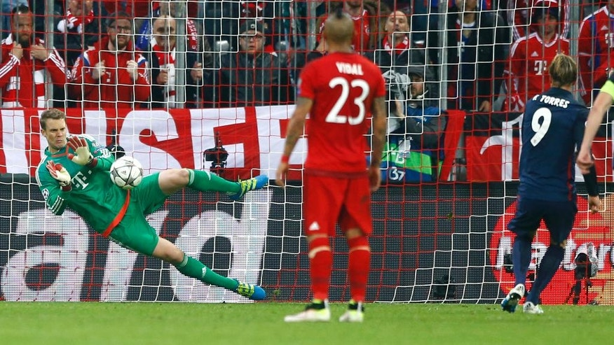 Bayern goalkeeper Manuel Neuer saves an Atletico's Fernando Torres penalty during the Champions League second leg semifinal soccer match between Bayern Munich and Atletico de Madrid in Munich, Germany, Tuesday, May 3, 2016. (AP Photo/Matthias Schrader)