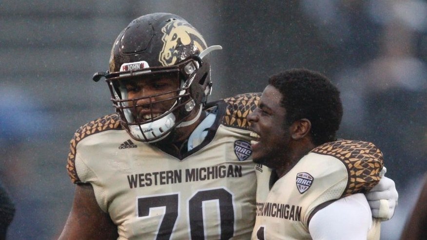 Nov 27, 2015; Toledo, OH, USA; Western Michigan Broncos offensive lineman Willie Beavers (70) celebrates with safety Rontavious Atkins (1) after the game against the Toledo Rockets at Glass Bowl. Broncos win 35-30. Mandatory Credit: Raj Mehta-USA TODAY Sports