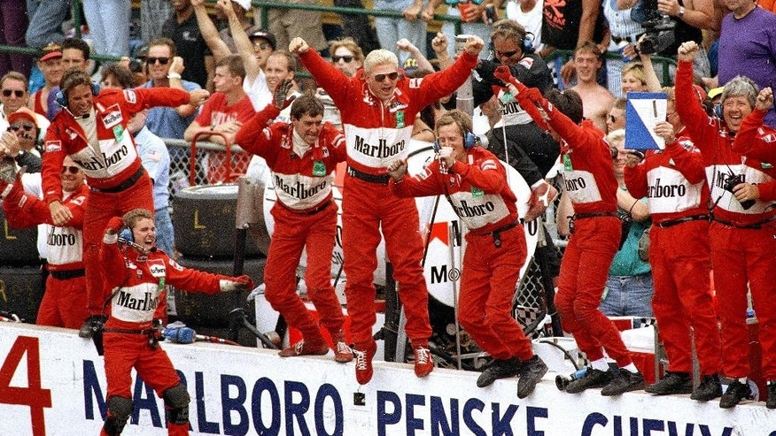 FILE - In this May 30, 1993 file photo, Emerson Fittipaldi's crew members jump from the pit wall after Fittipaldi drove his Penske-Chevrolet C to victory in the 77th running of the Indianapolis 500 auto race at Indianapolis Motor Speedway.  (AP Photo/ Tom Strickland, File)