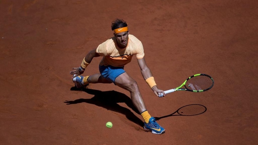 Rafael Nadal, from Spain, lunges to return a ball against Andrey Kuznetsov, from Russia, during a Madrid Open tennis tournament match in Madrid, Spain, Tuesday, May 3, 2016. Nadal won 6-3, 6-3. (AP Photo/Francisco Seco)