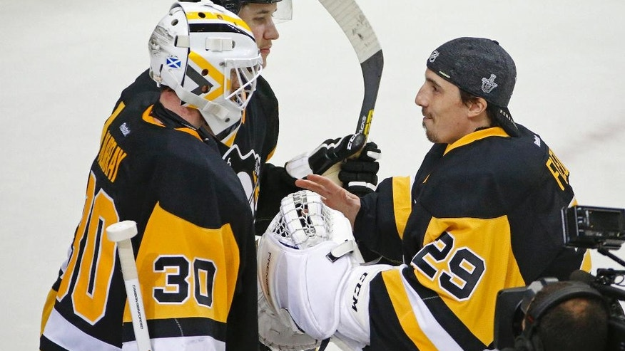 Pittsburgh Penguins goalie Marc-Andre Fleury (29) congratulates Pittsburgh Penguins goalie Matt Murray (30) after the Penguins defeated the Washington Capitals in Game 3 in an NHL hockey Stanley Cup Eastern Conference semifinals in Pittsburgh, Monday, May 2, 2016. (AP Photo/Gene J. Puskar)
