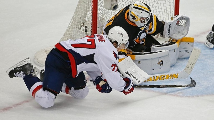 Washington Capitals T.J. Oshie (77) tries to slide the puck past Pittsburgh Penguins goalie Matt Murray (30) during the third period of Game 3 in an NHL hockey Stanley Cup Eastern Conference semifinals in Pittsburgh, Monday, May 2, 2016. (AP Photo/Gene J. Puskar)