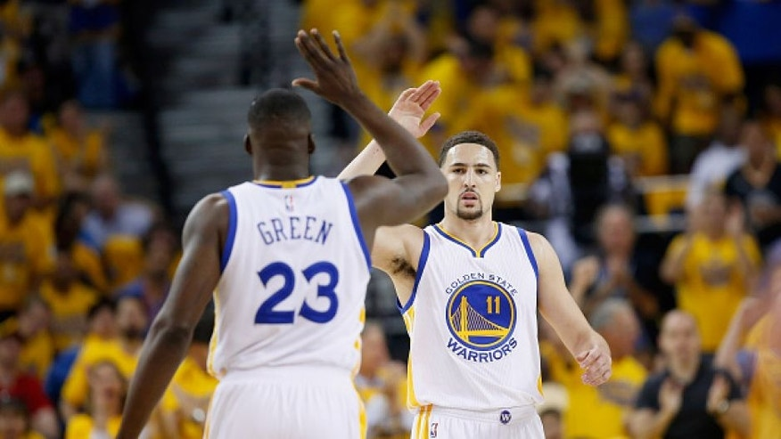 OAKLAND, CA - MAY 01: Klay Thompson #11 of the Golden State Warriors high-fives Draymond Green #23 during the first quarter against the Portland Trail Blazers during Game One of the Western Conference Semifinals for the 2016 NBA Playoffs at ORACLE Arena on May 01, 2016 in Oakland, California. NOTE TO USER: User expressly acknowledges and agrees that, by downloading and or using this photograph, User is consenting to the terms and conditions of the Getty Images License Agreement. (Photo by Ezra Shaw/Getty Images)