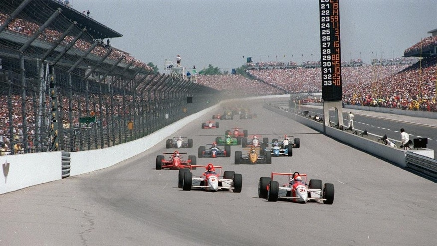 FILE - In this May 29, 1994 file photo, Al Unser Jr., driving his Penske-Mercedes (31), leads teammate Emerson Fittipaldi (2) into the first turn at the start of the 78th running of the Indianapolis 500 at Indianapolis Motor Speedway. (AP Photo/File)