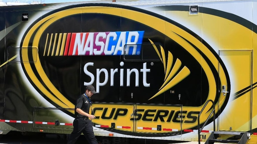 An auto racing worker walks past a NASCAR Sprint Cup series hauler at Kansas Speedway in Kansas City, Kan., Thursday, May 5, 2016. (AP Photo/Orlin Wagner)