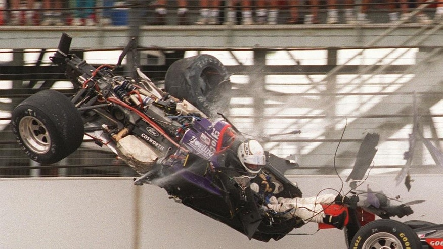FILE - In this May 28, 1995 file photo, Stan Fox, his legs exposed, sits in his airborne car after the front end was torn off while slamming into the first turn wall on the opening lap of the 1995 Indianapolis 500 auto race at Indianapolis Motor Speedway. Fox's car had collided with Eddie Cheever's, right, both hitting the wall.  (AP Photo/Martin Seppala, File)
