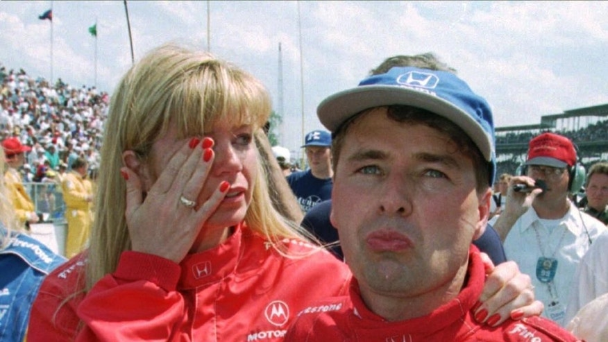 FILE - In this May 28, 1995 file photo, Scott Goodyear and his wife, Leslie, fight back tears after Goodyear was penalized for passing the pace car as he led late in the Indianapolis 500 auto race at Indianapolis Motor Speedway. (AP Photo/Michael Conroy, File)