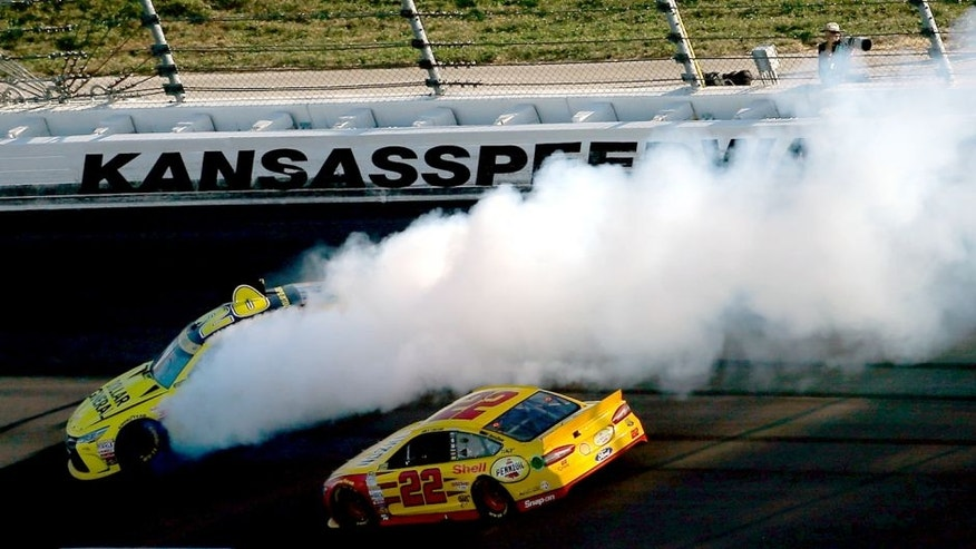 KANSAS CITY, KS - OCTOBER 18: Matt Kenseth, driver of the #20 Dollar General Toyota, spins as Joey Logano, driver of the #22 Shell Pennzoil Ford, races by during the NASCAR Sprint Cup Series Hollywood Casino 400 at Kansas Speedway on October 18, 2015 in Kansas City, Kansas. (Photo by Todd Warshaw/Getty Images)