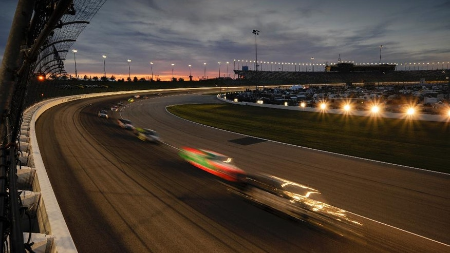 The trucks run under a Kansas sunset during a Camping World Truck Series race at Kansas Speedway in Kansas City, Kan., Friday, May 6, 2016. (AP Photo/Reed Hoffmann)