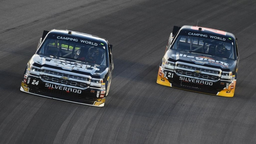 Camping World Truck Series driver Clint Bowyer (24) leads Camping World Truck Series driver Johnny Sauter (21) into the first corner during a Camping World Truck Series race at Kansas Speedway in Kansas City, Kan., Friday, May 6, 2016. (AP Photo/Reed Hoffmann)