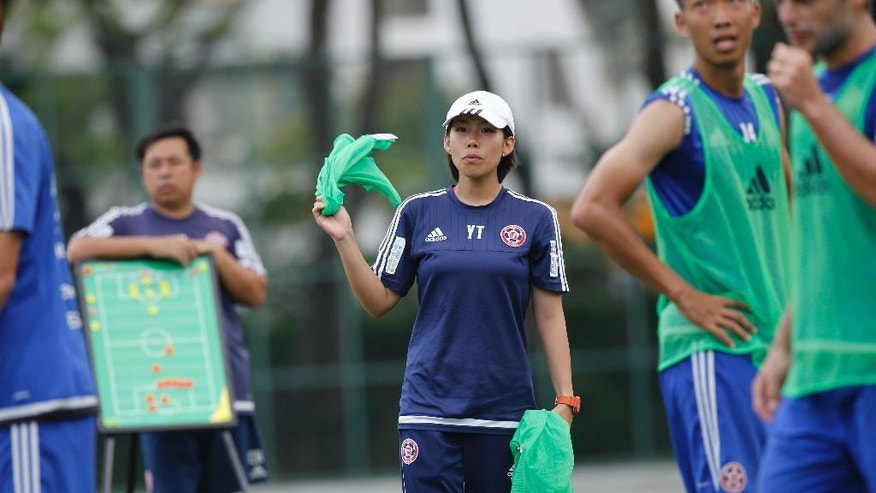Eastern Sports Club head coach Chan Yuen-ting, center, delivers jersey to her teammates during a training session in Hong Kong, Friday, May 6, 2016.  At age 27, Chan is younger than several of the players she coaches at Eastern Sports Club yet she has already secured a unique place for herself in soccer history by becoming the first woman to lead a men's team to a top-division national championship. Chan took charge at Eastern in December, with the club not having won the Hong Kong league for 21 years, and last month the team clinched that elusive title and made their female coach the talk of the town.(AP Photo/Kin Cheung)