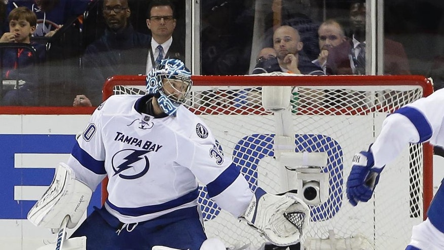 Tampa Bay Lightning goalie Ben Bishop (30) deflects a shot by the New York Islanders during the third period of Game 4 of the NHL hockey Stanley Cup Eastern Conference semifinals, Friday, May 6, 2016, in New York. (AP Photo/Frank Franklin II)