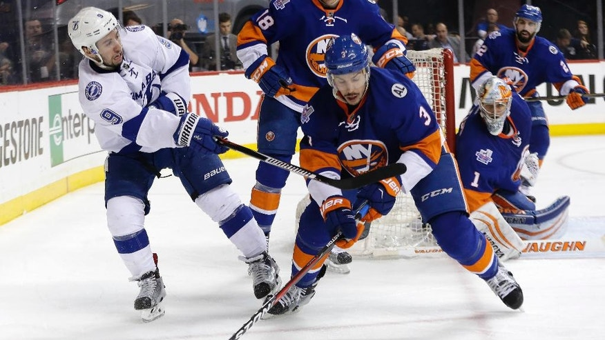 Tampa Bay Lightning center Tyler Johnson (9) passes off the puck against New York Islanders defenseman Travis Hamonic (3) during the third period of Game 4 of the NHL hockey Stanley Cup Eastern Conference semifinals, Friday, May 6, 2016, in New York. (AP Photo/Frank Franklin II)
