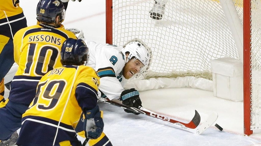 San Jose Sharks center Joe Pavelski (8) knocks the puck across the goal line as Nashville Predators' Colton Sissons (10) and Roman Josi (59), of Switzerland, defend during the first overtime period in Game 4 of an NHL hockey Stanley Cup Western Conference semifinal playoff series Thursday, May 5, 2016, in Nashville, Tenn. The goal was not allowed because of goaltender interference. (AP Photo/Mark Humphrey)