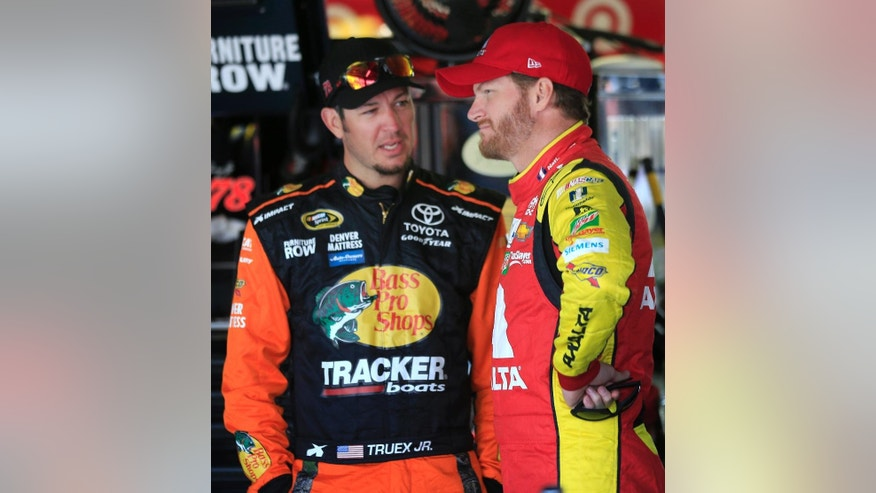 NASCAR drivers Martin Truex Jr., left, and Dale Earnhardt Jr. talks in the garage while waiting for Sprint Cup Series auto racing practice at Kansas Speedway in Kansas City, Kan., Friday, May 6, 2016. (AP Photo/Orlin Wagner)