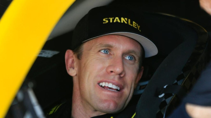 NASCAR driver Carl Edwards sits in his race car while waiting for Sprint Cup Series practice at Kansas Speedway in Kansas City, Kan., Friday, May 6, 2016. (AP Photo/Orlin Wagner)