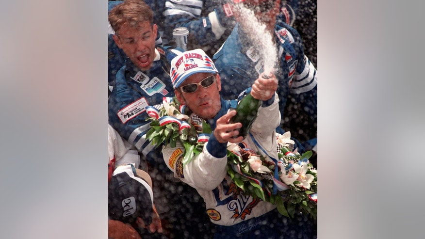 FILE - In this May 27, 1997 file photo, Arie Luyendyk sprays champagne after winning the 81st running of the Indianapolis 500 auto race at Indianapolis Motor Speedway. (AP Photo/Chuck Robinson, File)