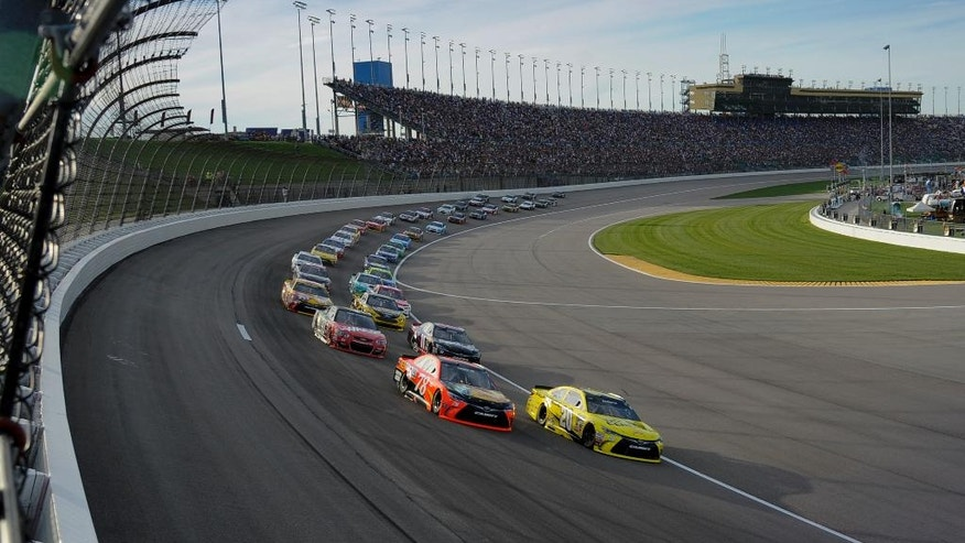 Martin Truex Jr. (78) and Matt Kenseth (20) lead the pack into the first corner at the start of a NASCAR Sprint Cup Series auto race at Kansas Speedway in Kansas City, Kan., Saturday, May 7, 2016. (AP Photo/Reed Hoffmann)