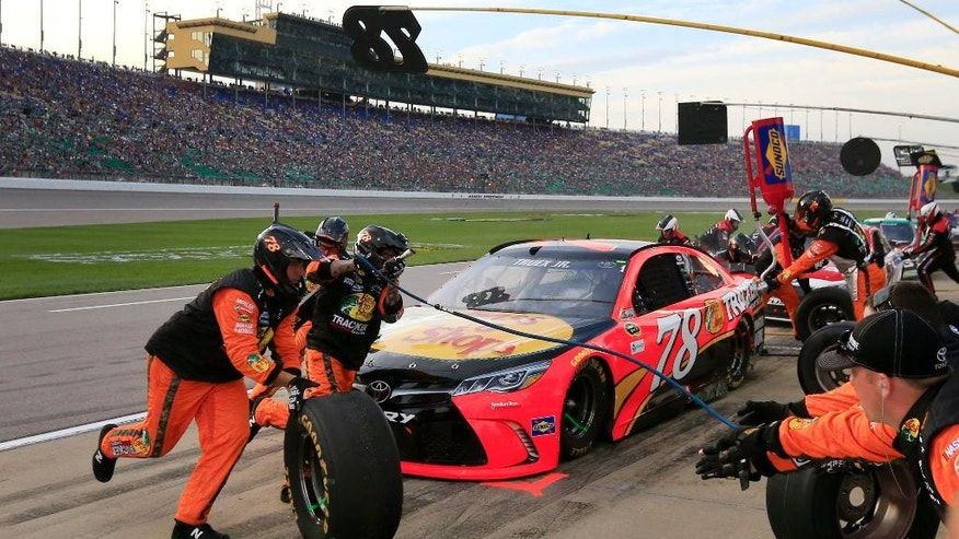 Martin Truex Jr. (78) pits during the MASCAR Sprint Cup Series auto race at Kansas Speedway in Kansas City, Kan., Saturday, May 7, 2016. (AP Photo/Orlin Wagner)