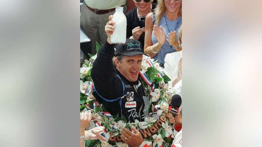 FILE - In this May 24, 1998 file photo, Indianapolis 500 winner Eddie Cheever hoists the traditional bottle of milk after winning the 82nd running of the race, in Indianapolis. (AP Photo/Michael Conroy, File)