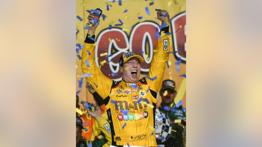 Kyle Busch celebrates after winning a NASCAR Sprint Cup Series auto race at Kansas Speedway in Kansas City, Kan., Saturday, May 7, 2016. (AP Photo/Reed Hoffmann)