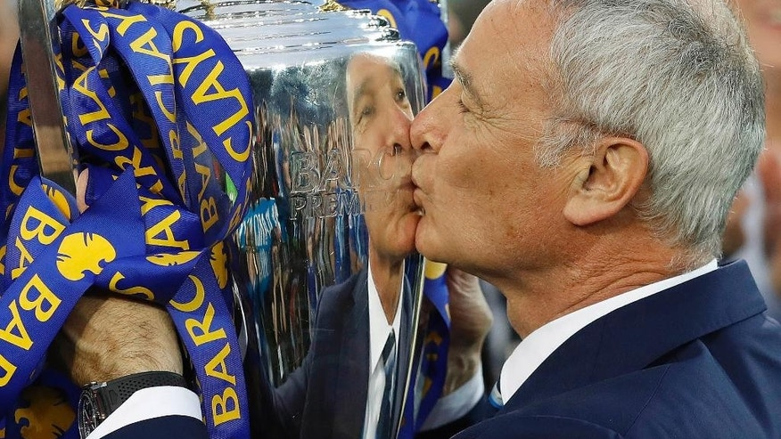 Leicester's team manager Claudio Ranieri kisses the trophy as Leicester City celebrate becoming the English Premier League soccer champions at King Power stadium in Leicester, England, Saturday, May 7, 2016.(AP Photo/Matt Dunham)