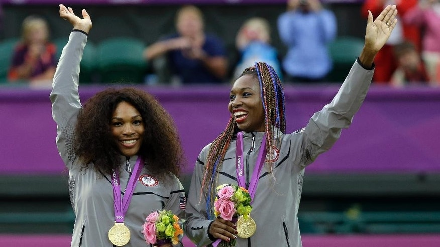 FILE -- In this file photo, taken on Aug. 5, 2012, at the London Summer Olympics, Serena Williams, left, and Venus Williams of the United States celebrate on podium after receiving their gold medals in women's doubles. The winningest team in Olympic tennis history has entered the doubles draw at this week's Italian Open to kick off their preparations for the Rio de Janeiro Games. (AP Photo/Elise Amendola)