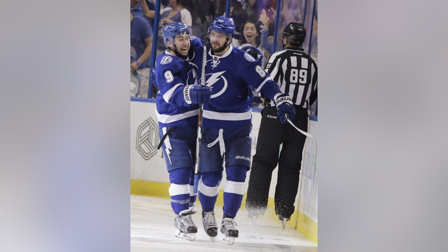 Tampa Bay Lightning's Tyler Johnson (9) congratulates teammate Nikita Kucherov (86), of Russia, after Kuchevov scored a goal during the third period of Game 5 of the NHL hockey Stanley Cup Eastern Conference semifinals against the New York Islanders, Sunday, May 8, 2016, in Tampa, Fla. (AP Photo/Chris O'Meara)
