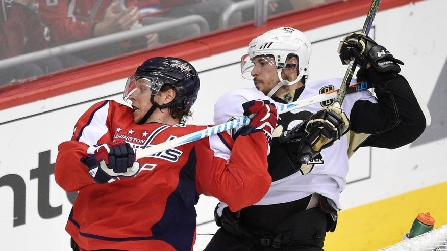 Pittsburgh Penguins center Sidney Crosby, right, holds onto the stick of Washington Capitals center Nicklas Backstrom, left, of Sweden, during the third period of Game 5 in an NHL hockey Stanley Cup Eastern Conference semifinals, Saturday, May 7, 2016, in Washington. The Capitals won 3-1. (AP Photo/Nick Wass)