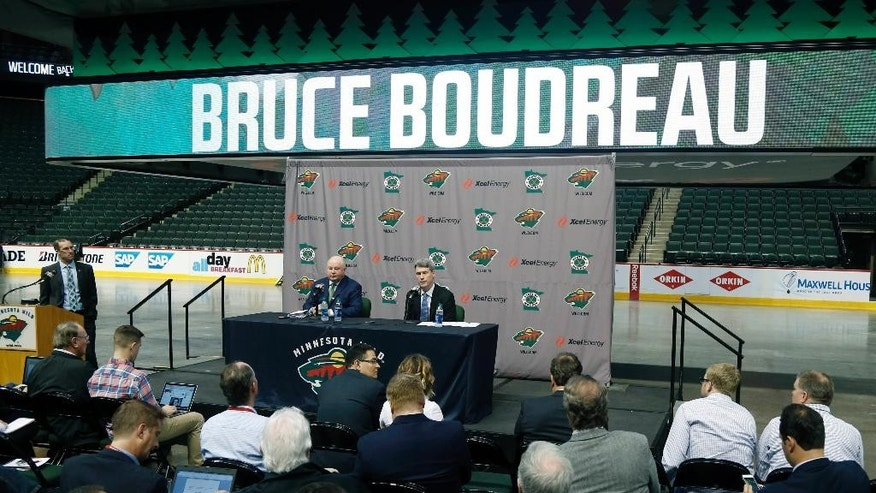 Bruce Boudreau, left, is introduced by Minnesota Wild general manager Chuck Fletcher, right, as the new Wild NHL hockey team head coach during a news conference Tuesday, May 10, 2016, in St. Paul, Minn. (AP Photo/Jim Mone)