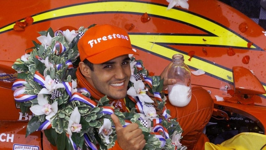 FILE - In this May 28, 2000 file photo, Juan Pablo Montoya of Colombia gives a thumbs-up while holding a bottle of milk after winning the 84th edition of the Indianapolis 500 auto race at Indianapolis Motor Speedway. (AP Photo/Michael Conroy, File)