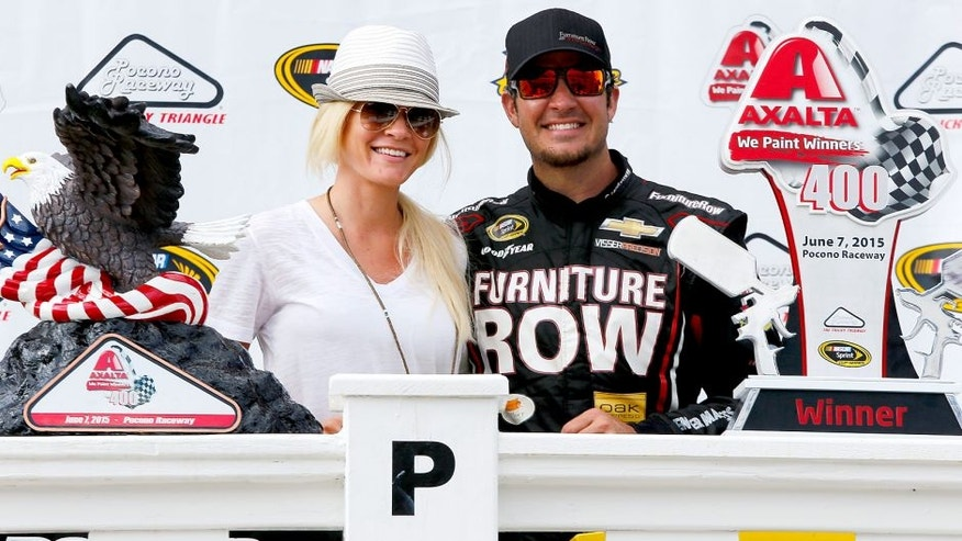 DOVER, DE - MAY 31: Martin Truex Jr., driver of the #78 Furniture Row/Visser Precision Chevrolet, right, and girlfriend Sherry Pollex take part in pre-race ceremonies for the NASCAR Sprint Cup Series FedEx 400 Benefiting Autism Speaks at Dover International Speedway on May 31, 2015 in Dover, Delaware. (Photo by Todd Warshaw/Getty Images)