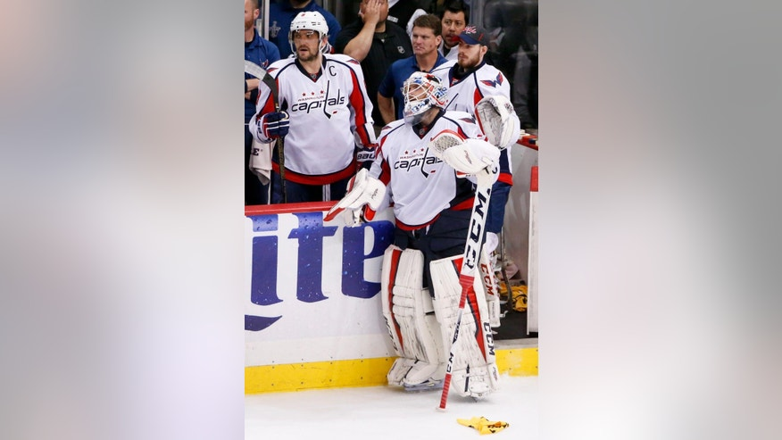 Washington Capitals goalie Braden Holtby (70) looks up toward the scoreboard while standing near Alex Ovechkin, left, after the Pittsburgh Penguins defeated the Capitals 5-4 in overtime of Game 6 of the NHL hockey Stanley Cup Eastern Conference semifinals, Tuesday, May 10, 2016, in Pittsburgh. The Penguins advanced to the conference finals. (AP Photo/Gene J. Puskar)
