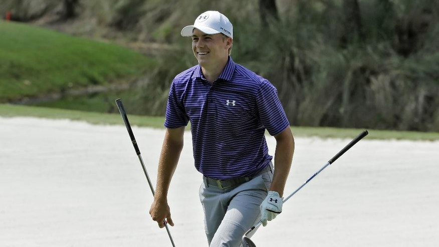 Jordan Spieth smiles after retrieving his sand wedge from a bunker on the 15th during a practice round for The Players Championship golf tournament Wednesday, May 11, 2016, in Ponte Vedra Beach, Fla. (AP Photo/Chris O'Meara)