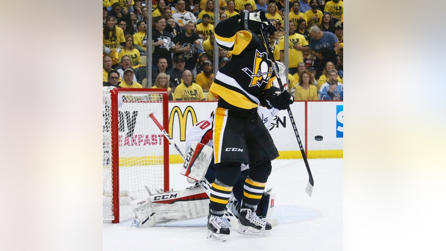 Pittsburgh Penguins' Carl Hagelin, right, deflects the puck as it goes by in front of Washington Capitals goalie Braden Holtby during the second period of Game 6 of the NHL hockey Stanley Cup Eastern Conference semifinals, Tuesday, May 10, 2016 in Pittsburgh. (AP Photo/Gene J. Puskar)