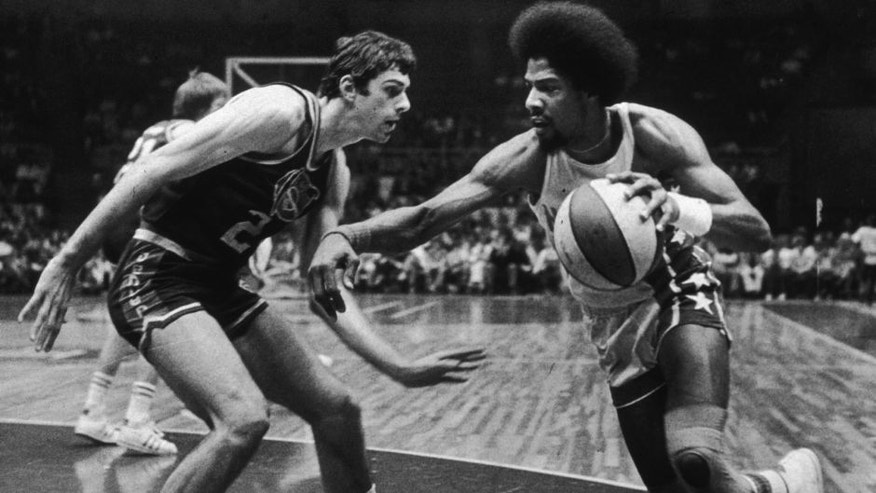 6th May 1976: American basketball player Julius Erving of the New Jersey Nets, nicknamed 'Dr J,' driving past Bobby Jones of the Denver Nuggets during a game. (Photo by Larry C. Morris/New York Times Co./Getty Images)