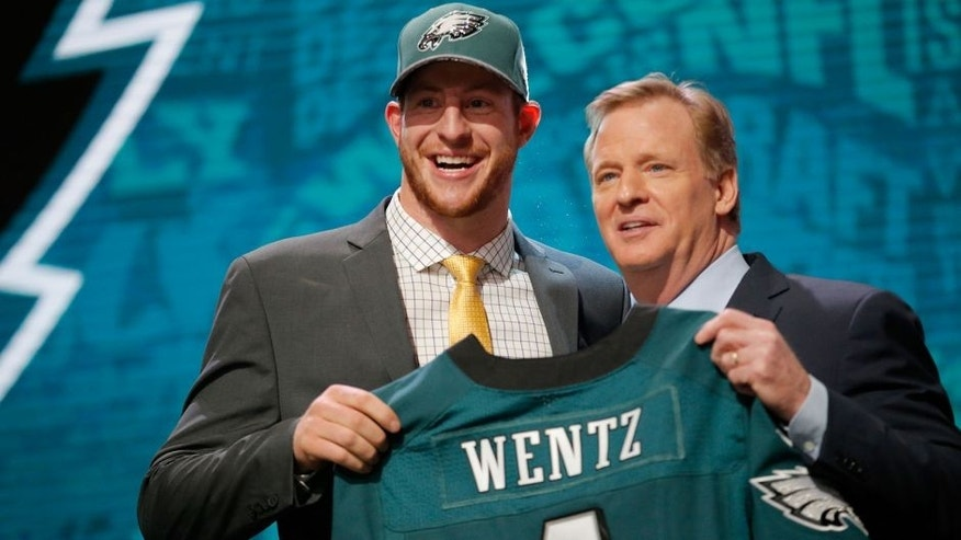 CHICAGO, IL - APRIL 28: (L-R) Carson Wentz of the North Dakota State Bison holds up a jersey with NFL Commissioner Roger Goodell after being picked #2 overall by the Philadelphia Eagles during the first round of the 2016 NFL Draft at the Auditorium Theatre of Roosevelt University on April 28, 2016 in Chicago, Illinois. (Photo by Jon Durr/Getty Images)