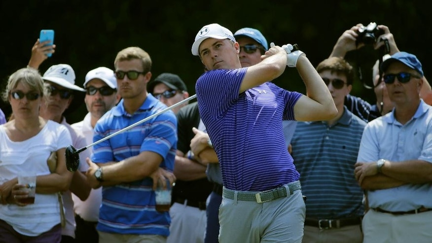 The gallery watches as Jordan Spieth hits his tee shot on the 15th hole during a practice round for The Players Championship golf tournament Wednesday, May 11, 2016, in Ponte Vedra Beach, Fla. (AP Photo/Chris O'Meara)