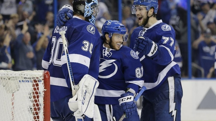 Tampa Bay Lightning's goalie Ben Bishop (30) is congratulated by Jonathan Marchessault (81) and Victor Hedman (77), of Sweden, at the end of the third period of Game 5 of the NHL hockey Stanley Cup Eastern Conference semifinals against the New York Islanders, Sunday, May 8, 2016, in Tampa, Fla. The Lightning defeated the Islanders 4-0, to advance  to the Eastern Conference finals. Hedman scored two of the goals. (AP Photo/Chris O'Meara)