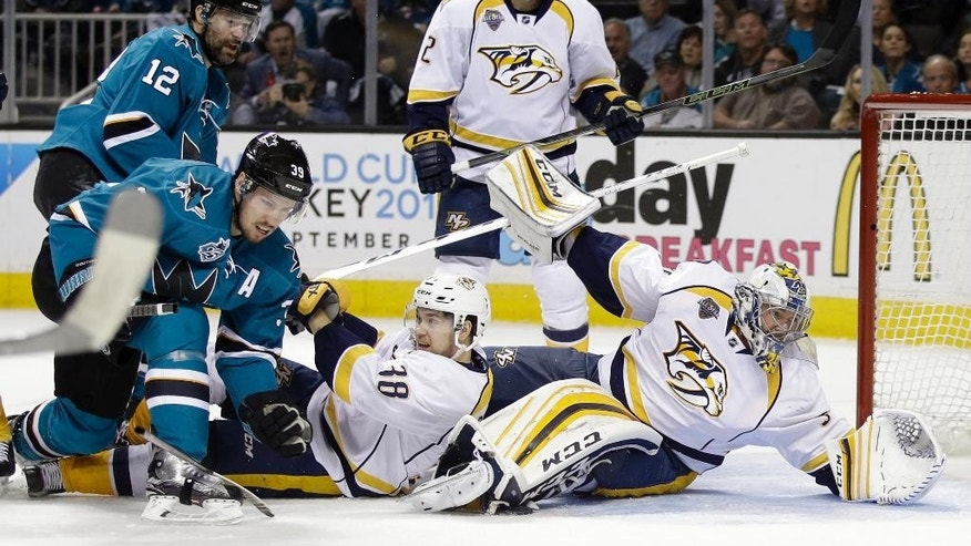 Nashville Predators goalie Pekka Rinne, right, falls down after deflecting a shot on goal next to teammate Viktor Arvidsson (38) and San Jose Sharks' Logan Couture (39) during the first period of Game 7 in an NHL hockey Stanley Cup Western Conference semifinal series Thursday, May 12, 2016, in San Jose, Calif. (AP Photo/Marcio Jose Sanchez)