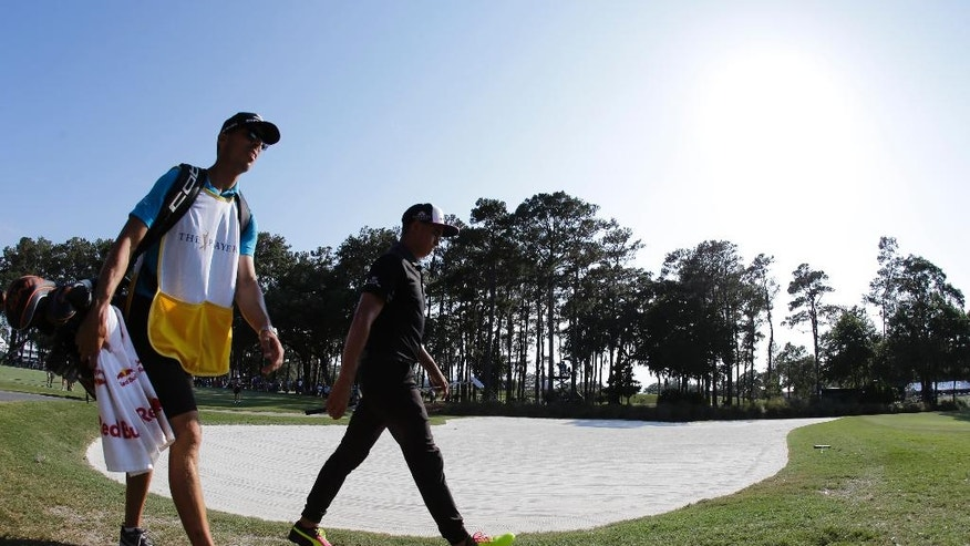 Rickie Fowler and his caddie Joe Skovron walk around a bunker on the 15th hole during the first round of The Players Championship golf tournament Thursday, May 12, 2016, in Ponte Vedra Beach, Fla. (AP Photo/Chris O'Meara)